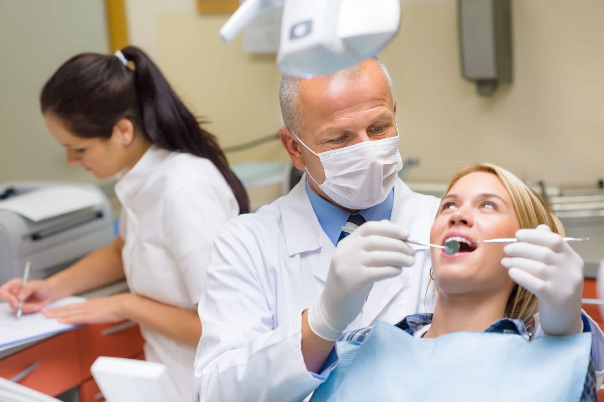 Professional dentist doing teeth checkup on female patient dental surgery